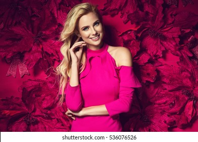 Beautiful young elegant woman in sexy pink dress posing over red background with poinsettia holding present. Christmas fashion photo