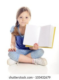 A beautiful young elementary girl sitting cross-legged on the floor while showing the viewer the open pages (left blank for your text) of her book.  On a white background.