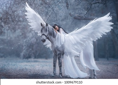 Beautiful, young elf, walking with a unicorn. Angel is wearing an incredible light white dress. The ice queen lies on the horse. Black hair. Concept Sleeping Beauty. Art Photography cold winter nature
