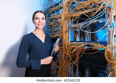 Beautiful young engineer with clipboard in server room