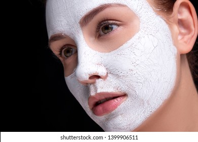 Beautiful young european woman apply clay mask on her face. beauty spa concept