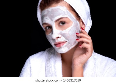 Beautiful young european woman apply clay mask on her face with towel on her head. beauty spa concept