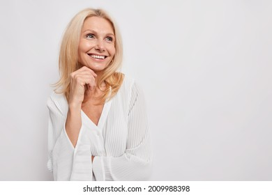 Beautiful young European woman of middle age smiles gently keeps hand under chin looks away with dreamy expression wears silk blouse isolated over white background copy space for advertisement