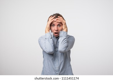 beautiful young european woman is shocked because of the bad news, isolated on a gray background