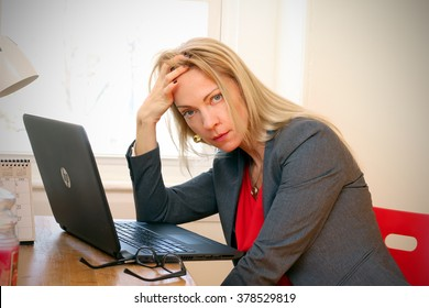 Beautiful young exhausted woman in office.