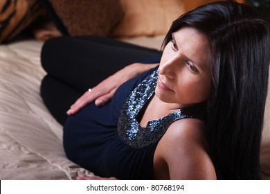 Beautiful young expectant mom relaxes on a bed