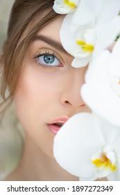 Schönes Gesicht der jungen Frau mit perfekter Haut und Make-up Bedeckung Teil ihres Gesichts durch tropische Orchidee.  Frühlingskonzept für Spa, Hautpflege und Wellness. Nahaufnahme, selektiver Fokus.