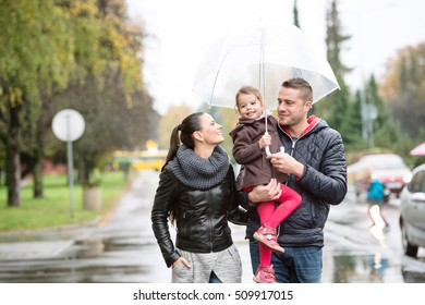Beautiful young family with daughter under the umbrella. Walking in the street on a rainy day.