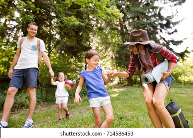 Beautiful young family with daughters going camping in forest.