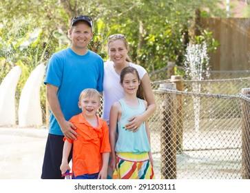 Beautiful young family enjoying a day at an outdoors amusement park