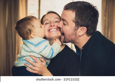 Beautiful young family. Father and son kissing the mother