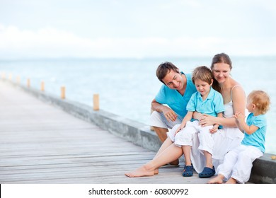 Beautiful young family of four sitting outdoors at seashore
