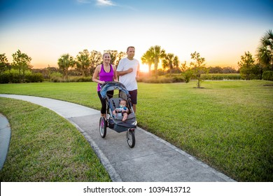 Beautiful young family jogging together outdoors along a pathway at a city park.