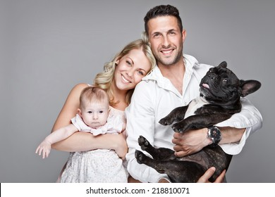 beautiful young family with little baby and dog isolated over grey background