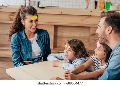 beautiful young family playing guess sticker in cafe
