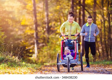 Beautiful young family running outside in autumn nature