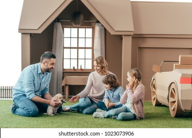 beautiful young family sitting on yard of cardboard house with their puppy