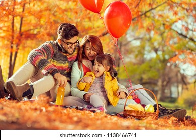 Beautiful young family sitting on a picninc blanket, having fun and enjoying an autumn day in the park