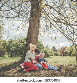 Beautiful young family of three people resting under a tree in summer park