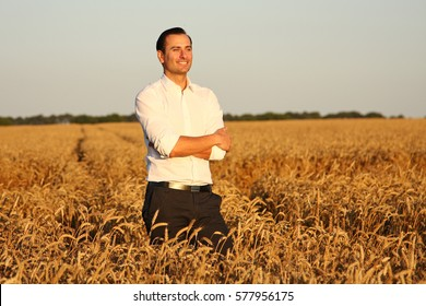 Beautiful and young farmer enjoys in wheat income during the harvest. The background is golden wheat field.