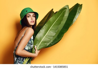 Beautiful young fashion girl with perfect skin in green hat hold tropical banana leaf in hands and covers a part of her face on yellow background