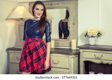 Beautiful young fashion model in blue and red and scottish cell dress and makeup and hairstyle posing next to commode smiling and looking at camera in provence design interior.