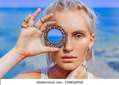 beautiful young fashion model on the beach. Close up portrait of boho model holding small mirror at her eye