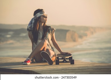 Beautiful young fashion skater girl looking at the sunset