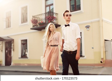 Beautiful young fashion stylish couple walking on the street in city old town together in summer evening ready to night party and have fun with love
