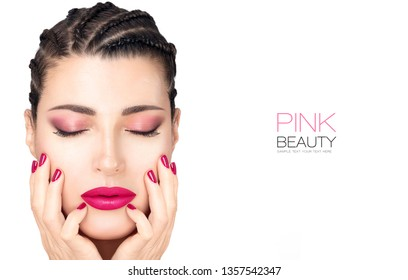 Beautiful young fashion woman with braided hair wearing matching trendy pink lipstick, nail polish and eye shadow. Beauty and makeup concept. Closeup face isolated on white with copy space.