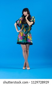 Beautiful young fashion woman in colorful dress Flirty posing on a blue background.