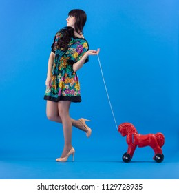 Beautiful young fashion woman in colorful dress pulling the rope toy red horse on a blue background.