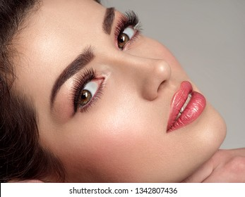 Beautiful young fashion woman with fashionable makeup. Attractive white girl with a long eyelashes.  Glamour fashion model with bright gloss make-up posing at studio. Stylish fashionable concept.