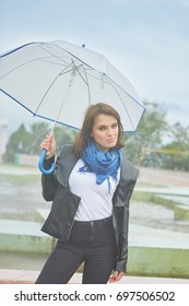 Beautiful young Fashion woman outdoors With umbrella near the fountain.
