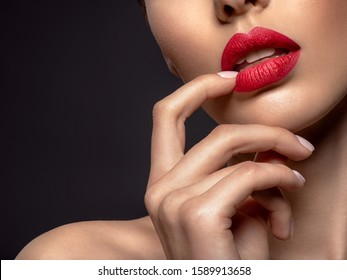 Beautiful young fashion woman with red lipstick. Glamour fashion model with bright gloss make-up  posing at studio. Part of female face.