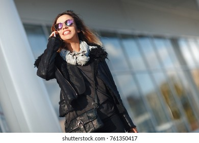 Beautiful young fashion woman with shopping bags near shop window calling smart phone, toned