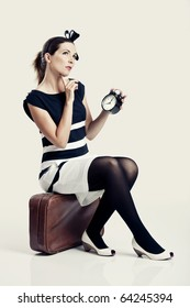 Beautiful young fashion woman sitting over a suitcase and holding a clock