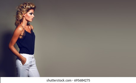 Beautiful young fashionable girl in fashionable clothes in a studio .Hairstyle - styling, bright makeup.