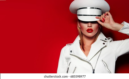 Beautiful young fashionable girl in a white cap and white jacket on a red background with red lips and nails.Fashion, beauty, cosmetics. Makeup, smooth skin.Advertisement, magazine.