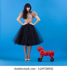 Beautiful young fashionable woman in a black skirt and a Flirty posing with a toy red horse on a blue background.