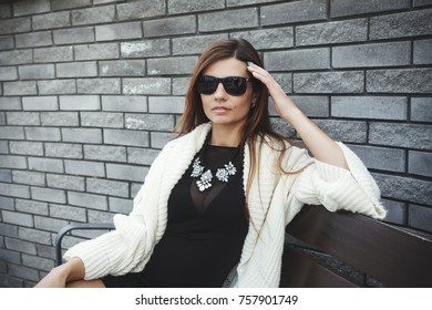Beautiful young fashionable woman in a black short dress and sunglasses posing in the city. Fashion photo