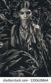 beautiful young fashionable woman with make up and stylish boho accessories posing on natural tropical background. Black and white