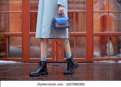 Beautiful young fashionable woman on the city street. She is wearing grey wool coat, dress, black boots and grey socks, she is holding fashion handbag in hand. Street style.