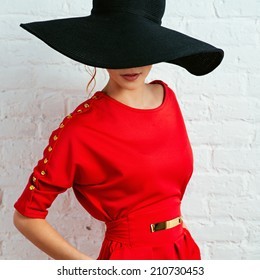 Beautiful young fashionable woman posing in red dress and black hat. Vogue style. Photo with instagram style filters