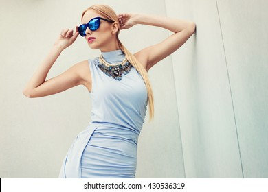 Beautiful young fashionable woman in sexy stylish dress, big necklace, blue sunglasses,  posing in the city.. Fashion photo