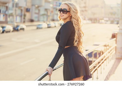A beautiful young fashionable woman smiling while standing in urban surroundings