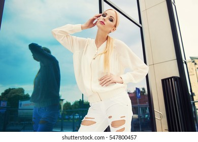 Beautiful young fashionable woman in stylish white ripped jeans, big necklace, posing in the city. Fashion photo