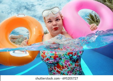 Beautiful young fat woman relaxing in the pool with lifebuoy