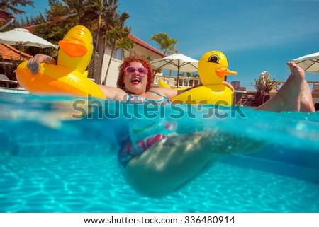 Naked toddler girl in rubber swimming pool