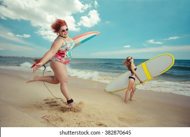 Beautiful young fat woman is runing to the summer sea with the surfboard